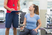 Personal trainer working with client holding dumbbell — Stock Photo