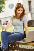 Woman with disposable cup and laptop sitting on bench — Stock Photo