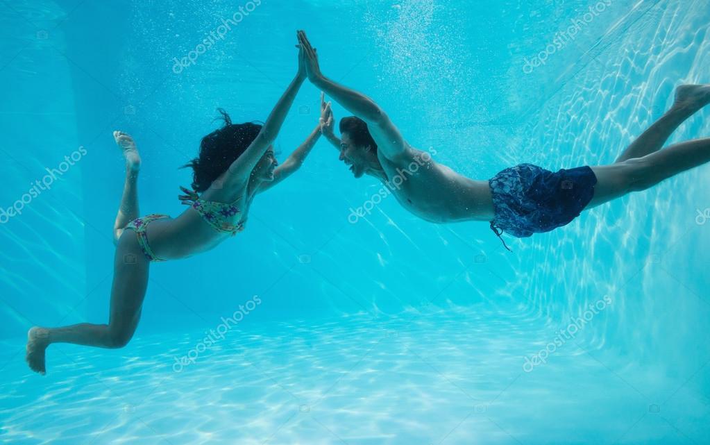 Pareja cogidos de la mano y nadando bajo el agua foto de Imagenes de hoteles bajo el agua
