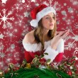 Composite image of sexy santa girl blowing over hands — Stock Photo #57149883