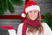 Composite image of festive blonde presenting with hand — Stock Photo