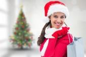 Composite image of festive brunette holding shopping bag — Stock Photo