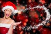 Composite image of woman wearing santa hat — Stock Photo