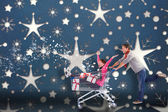 Composite image of man pushing woman in trolley — Stock Photo