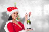 Composite image of woman holding a champagne bottle — Stock fotografie