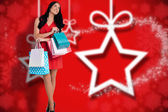 Composite image of woman standing with shopping bags — Stock Photo