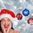 Composite image of surprised woman wearing santa hat — Stock Photo #57150853