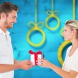 Composite image of young couple with gift — Stock Photo #57153815