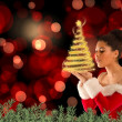 Santa girl blowing over her hands — Stock Photo #57155935