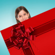 Cute girl showing card with christmas ribbon — Stock Photo #57157541