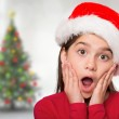 Composite image of festive little girl looking surprised — Stock Photo #57158753
