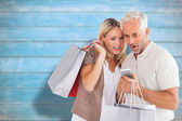 Happy couple with shopping bags and smartphone — Stock Photo