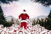Composite image of santa standing on pile of gifts — Stock Photo