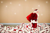 Composite image of santa walking on pile of gifts — Stock Photo