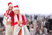 Happy festive couple with gifts and bags — 图库照片