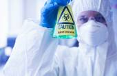 Scientist in protective suit holding beaker — Stock Photo