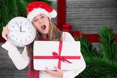 Festivo rubia mostrando un reloj y un regalo — Foto de Stock