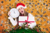 Composite image of festive blonde showing a clock and gift — Stock Photo