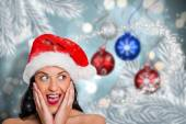 Composite image of surprised woman wearing santa hat — Stock Photo