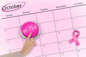 Hand pushing pink button for breast cancer awareness — Stock fotografie