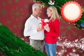 Composite image of loving couple with gift — Stock Photo