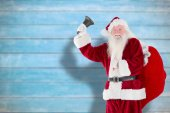 Composite image of santa claus ringing bell — Stock Photo