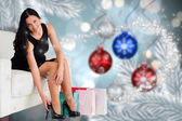 Composite image of woman sitting with shopping bags — Stock Photo
