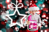 Composite image of festive boy holding a gift — Stock Photo
