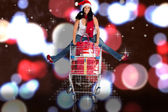 Composite image of woman jumping with shopping trolley — Stock Photo