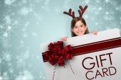 Composite image of festive little girl showing card — Stock Photo