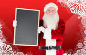 Composite image of santa claus showing blackboard — Stock Photo