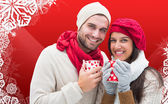Composite image of winter couple holding mugs — Foto de Stock