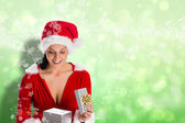 Composite image of smiling woman opening christmas present — Fotografia Stock