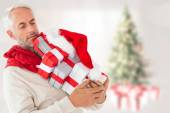 Composite image of happy festive man with gifts — Stock Photo
