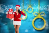 Composite image of woman smiling with christmas presents — Stock Photo