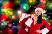 Composite image of woman smiling with christmas presents — Fotografia Stock