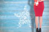 Composite image of classy woman holding a gift — Stock Photo