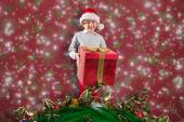 Composite image of festive boy holding gift — Stock Photo