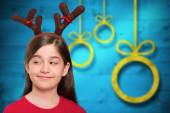 Composite image of festive little girl wearing antlers — Stock Photo