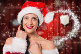 Composite image of smiling woman wearing a santa hat — Stok fotoğraf
