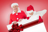 Composite image of festive couple showing poster — Stockfoto