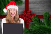 Composite image of festive blonde showing a laptop — Stok fotoğraf