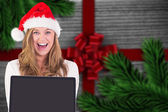 Composite image of festive blonde showing a laptop — Fotografia Stock