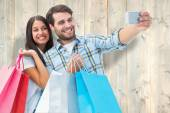 Composite image of happy couple taking a selfie — Stock Photo