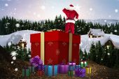 Composite image of santa standing on giant present — Stock Photo