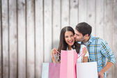 Composite image of happy couple with shopping bags — Stock Photo
