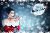 Santa girl blowing over her hands — Photo