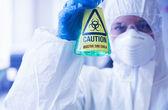 Scientist in protective suit holding beaker — Стоковое фото