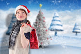 Composite image of smiling woman wearing santa hat — Stock Photo