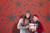 Composite image of couple smiling and holding gift — Foto de Stock